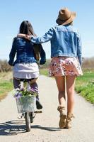 duas mulheres jovens com uma bicicleta vintage no campo.