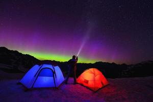 aurora boreal e tendas na montanha de neve foto