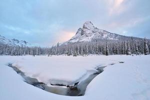 início do inverno coberto de neve sino da liberdade montanha foto