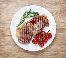 bife do lombo com alecrim e tomate cereja em um prato foto