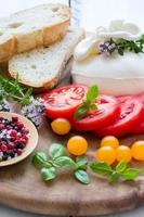 burrata italiana fresca e tomates variados em uma placa de madeira foto