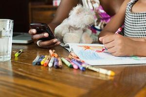 menina desenhando com giz de cera foto