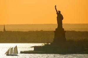 barco navegando ao lado da estátua da liberdade foto