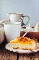 torta de pêssego quebrada e xícara de chá foto
