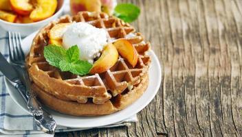 waffles belgas com sorvete e pêssegos frescos foto