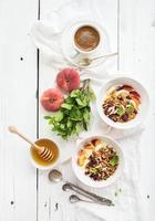 café da manhã saudável. tigela de granola de aveia com iogurte, frutas frescas foto