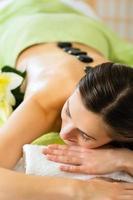 mulher tendo bem-estar massagem com pedras quentes foto