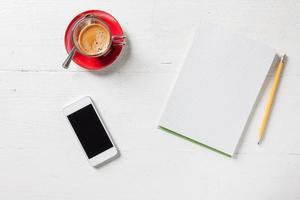 caderno de papel com lápis, café e telefone na mesa de madeira foto