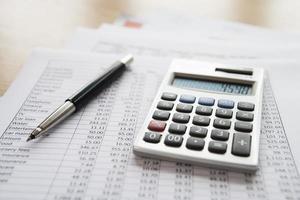 calculadora e caneta em documentos de finanças pessoais foto