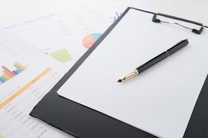 documento financeiro e caneta na mesa de escritório foto