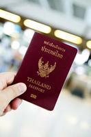 mão segurando o passaporte da tailândia foto