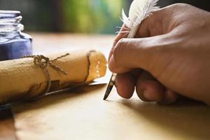 mão escrevendo usando caneta de pena