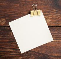 clipe e nota de papel na madeira foto