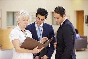 três consultores discutindo notas de pacientes no hospital