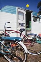 cruzadores de praia, sentado fora de um trailer de viagens vintage