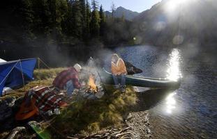 homem e mulher acampar na pequena ilha foto