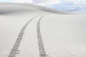 trilhas de pneu através de dunas de areia branca