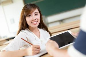 dois estudantes asiáticos discutem o conteúdo no tablet foto
