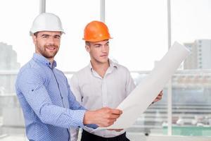 alegres jovens construtores estão olhando para esboços de construção foto