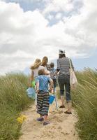 família caminhando juntos na praia