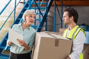 gerente de armazém e trabalhador falando juntos foto