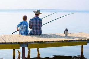 menino e seu pai pescando juntos foto