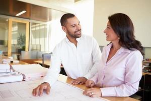arquitetos estudando juntos planos no escritório moderno