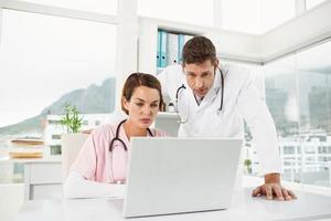 médicos usando laptop juntos no consultório médico foto