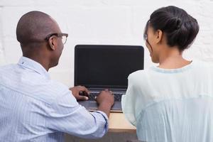 equipe de negócios trabalhando felizes juntos no laptop foto