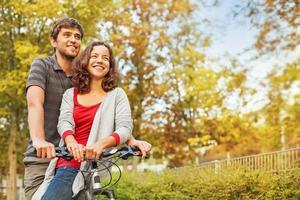 pessoas apaixonadas - andando juntas na mesma bicicleta foto