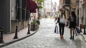 dois amigos na rua com sacolas de compras