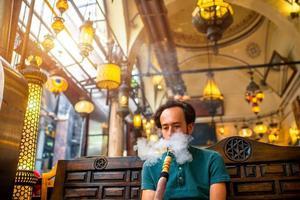 homem fumando cachimbo de água turco foto