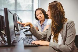 empresárias sérias, olhando para a tela do computador juntos foto