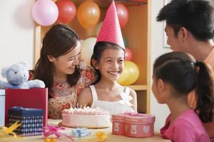 família comemorando o aniversário da menina foto