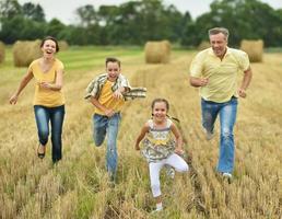 família feliz no campo de trigo