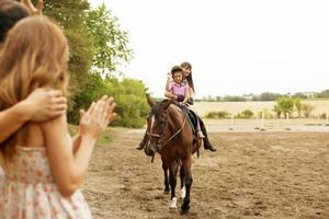 criança andar a cavalo ao ar livre. foto