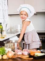 criança sorridente, cozinhar sopa foto