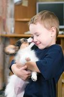 filhote de cachorro lambendo o rosto da criança foto