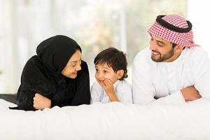 jovem família muçulmana, deitada na cama foto