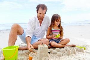 criança feliz castelo de areia foto