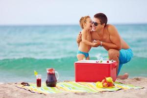família feliz no piquenique na praia de verão foto