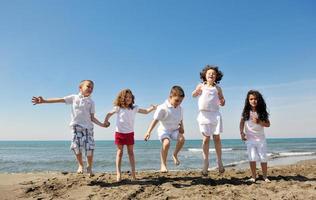 grupo criança feliz jogando na praia foto