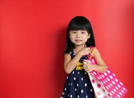criança com sacolas de compras foto