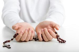 mãos de criança oferecem rosário de madeira