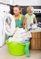 mulher com criança perto da máquina de lavar roupa foto