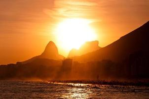 pôr do sol atrás das montanhas na praia de copacabana foto