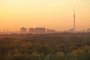 torre de tv e casas urbanas no nascer do sol laranja quente foto