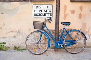 bicicleta estacionada sob sinal proibindo estacionamento, milão, itália foto
