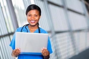 médico feminino americano africano segurando computador portátil foto