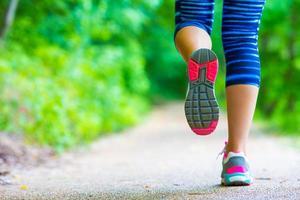 sapato de pés de mulher atleta corredor correndo na estrada foto